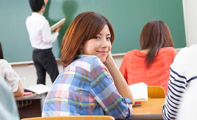 授業を受けながら振り返る女子大生