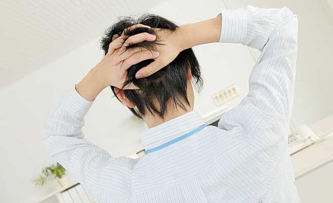 頭を抱え込む職場の男性