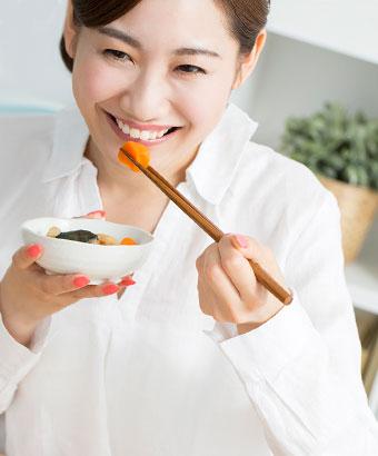 野菜の煮物を食べる女性