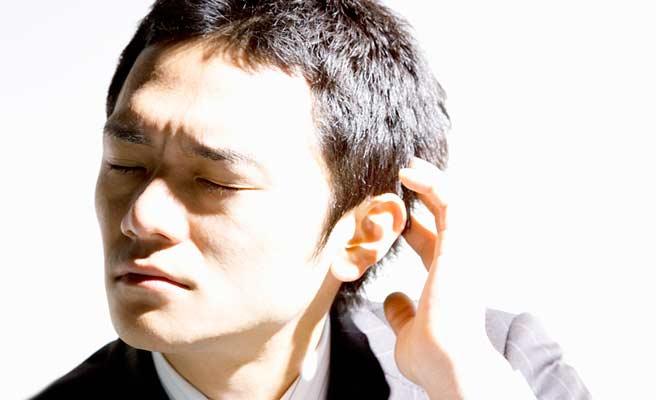 つまらなそうな顔をして側頭部を掻いてる男性