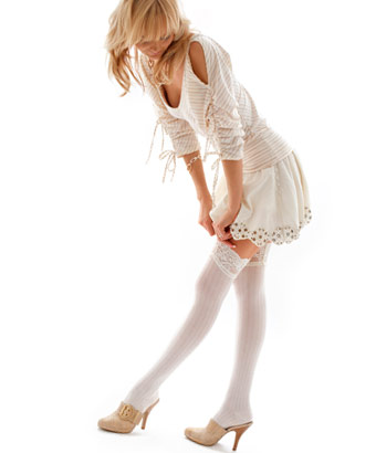 スカートとヒールを身に着けてストッキングを上げる女性