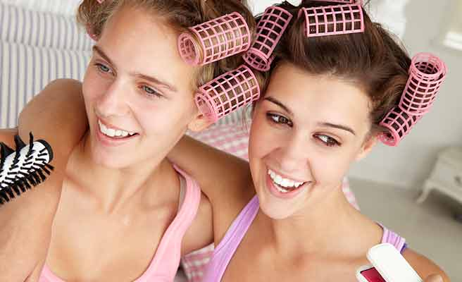 一緒にヘアーカラーを巻いて肩を組む女友達