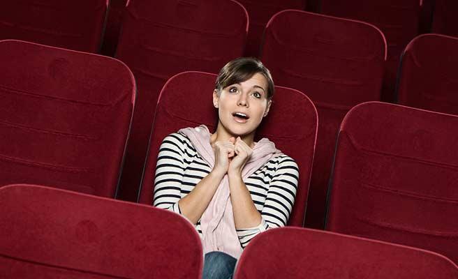 映画館の座席に一人座り楽しそうな女性