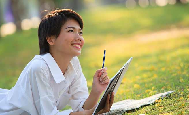 公園の芝生で寝そべりながらノートをとる女性