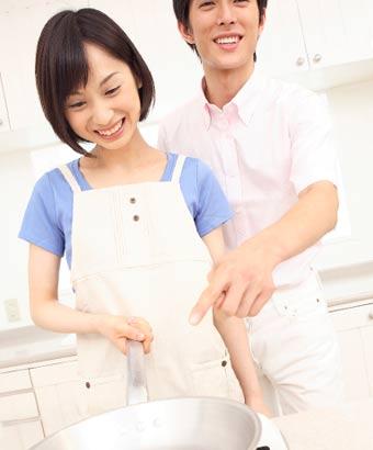夫に料理を教える妻