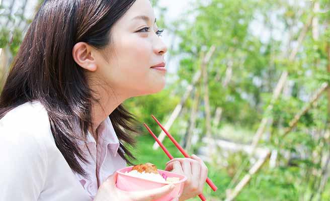 外で自前の弁当を食べる女性
