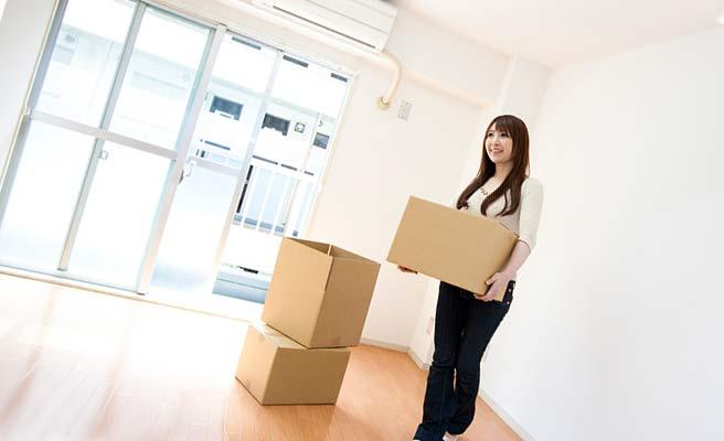 段ボール箱が置かれた部屋で荷物を持つ女性