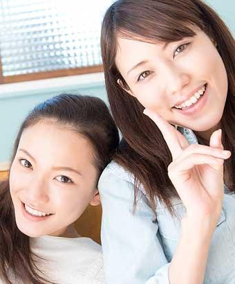 笑顔で友達と寄り添う女性