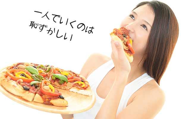 大きなピザを一人で食べる女性