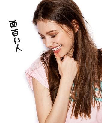 笑いながら顎に手をやる女性