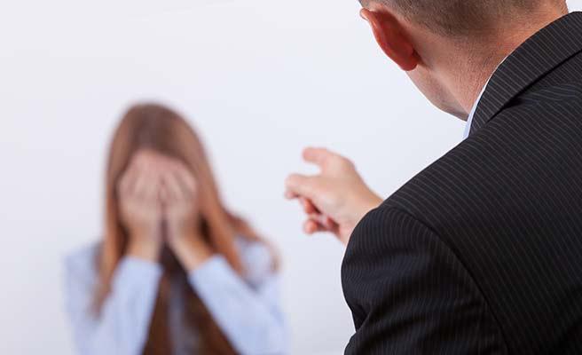 両手で顔を隠す女性に指さしながら小言を言う男性