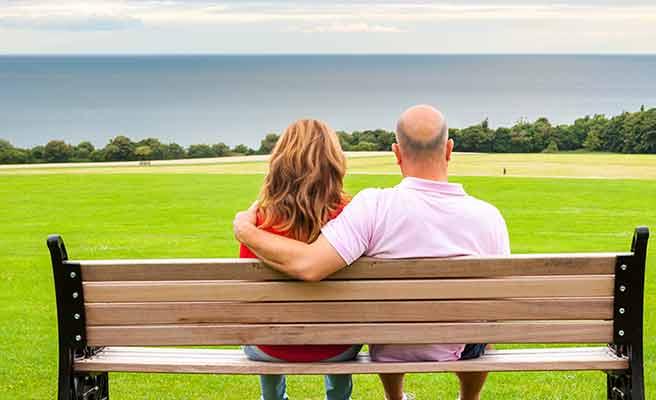 禿げた男性とベンチに並んで座る女性
