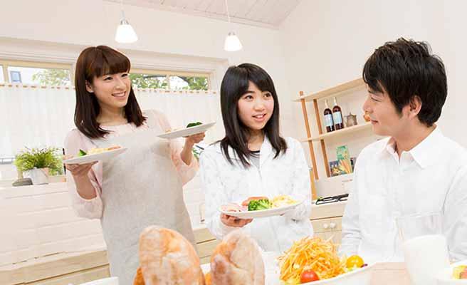 食卓のお父さんに料理を運んでくる母親と娘