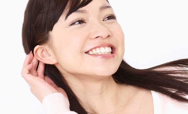 髪を耳の後ろにあげながら微笑む女性
