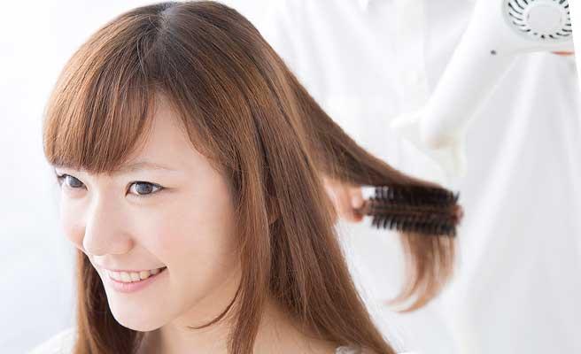 髪の手入れをする女性
