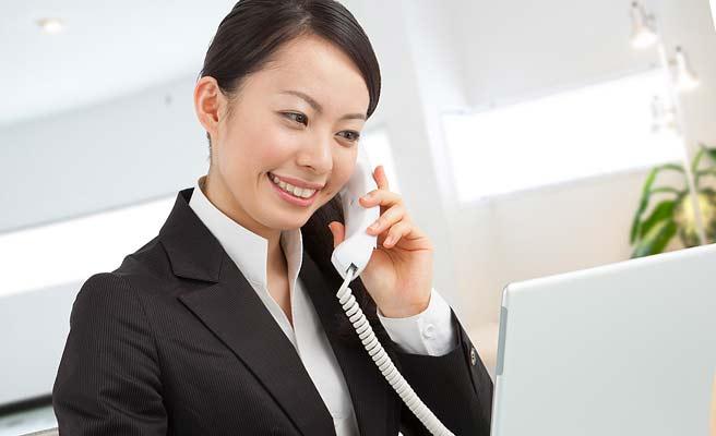 デスクで電話をしながらパソコンを操作するスーツ姿の女性