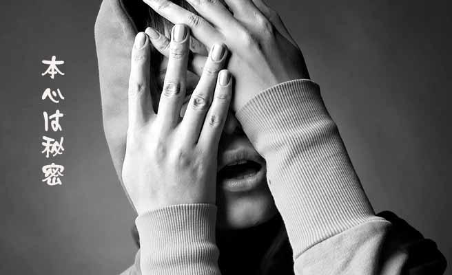 両手で顔を隠す女性