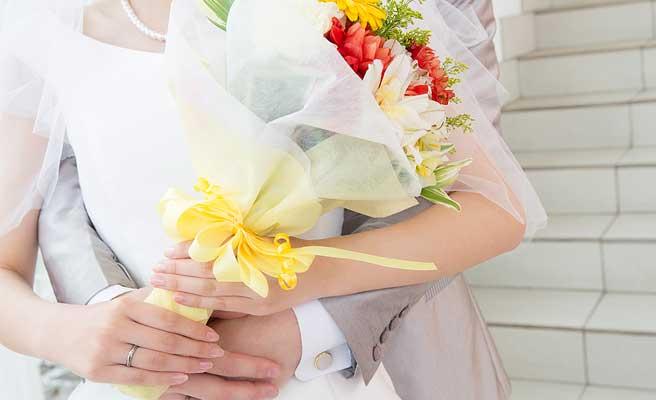 花束を持つ花嫁を抱きしめる新郎