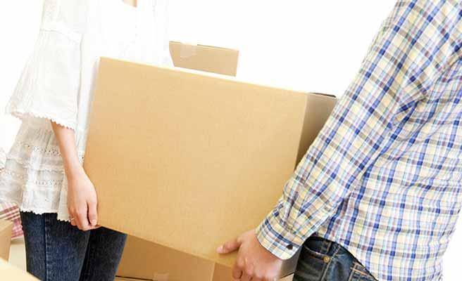 男女が大きな段ボール箱を二人で運ぶ