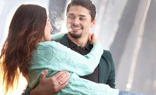お姫様抱っこされる女性、男性の首に両手をまわす