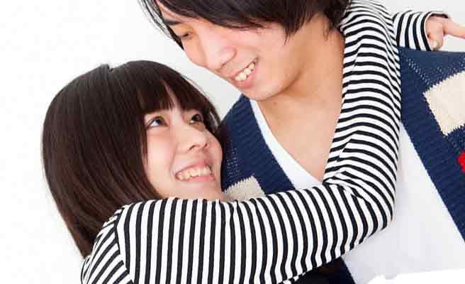 彼氏の首に腕を回す笑顔の女性
