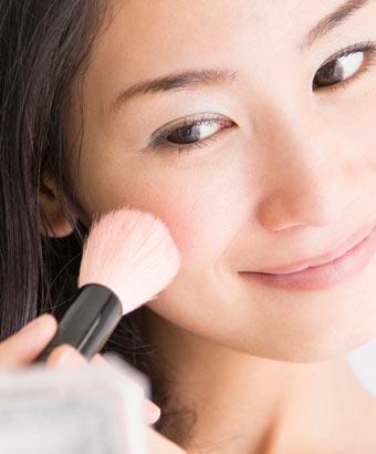ピンクチークで頬をメイクする女性