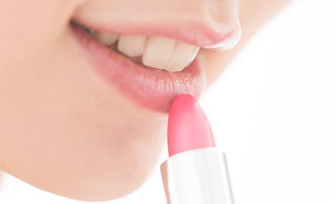 唇に口紅を塗る女性