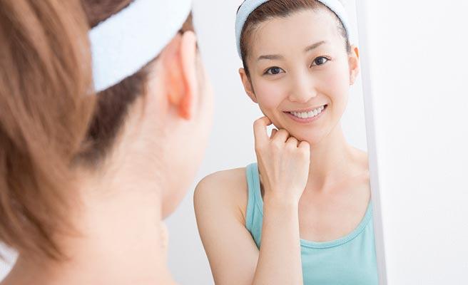 鏡の前で肌の手入れをする女性