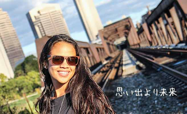 線路を背景に立つ女性
