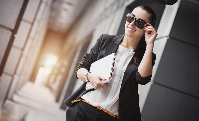 ノートパソコンをもって街を歩く女性