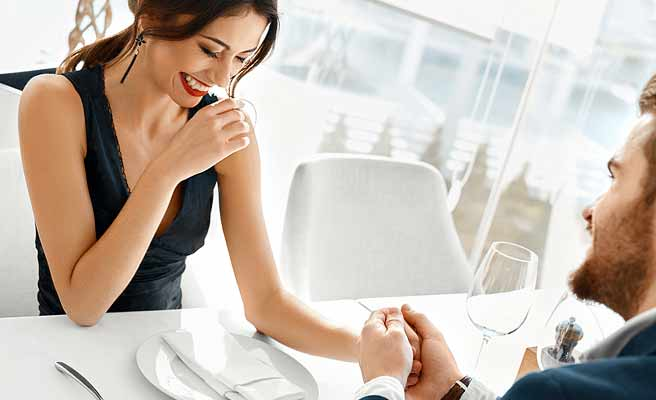 レストランで記念日を祝う男性が女性の手を握る