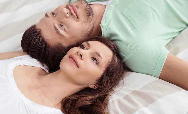 彼氏とベッドの上で頭を並べて横になる女性