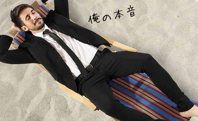 スーツ姿のまま砂浜に寝そべる男性