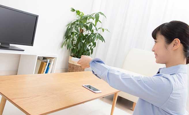 居間で一人でテレビをつける女性