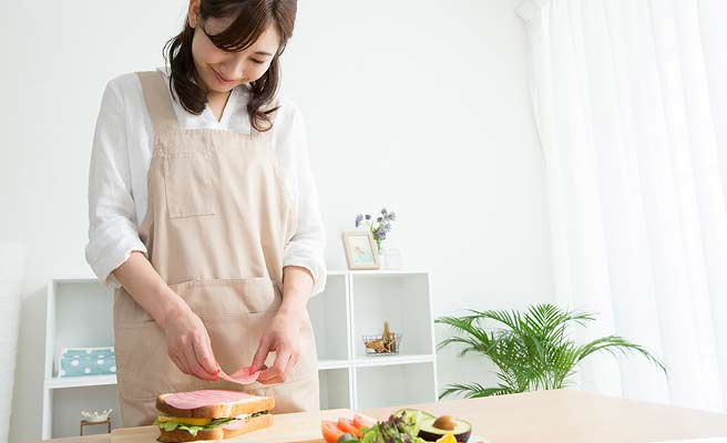 サンドイッチを作る楽しそうな女性