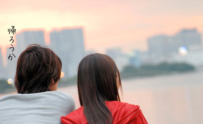 夕暮れの街を見ながら帰ろうかという男性と無言の女性