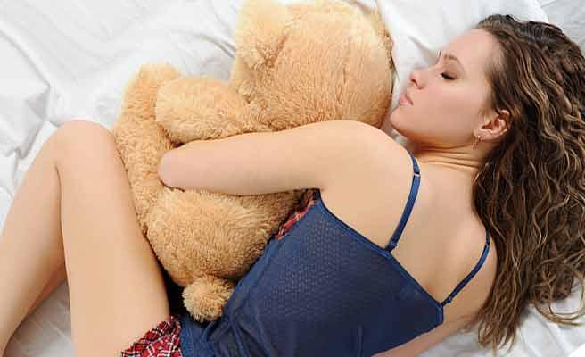 ぬいぐるみを抱いて眠る女性