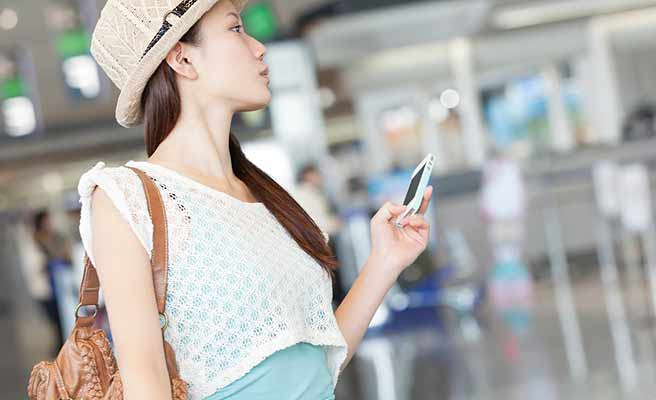 空港でスマホを持ちながら掲示板を見る女性