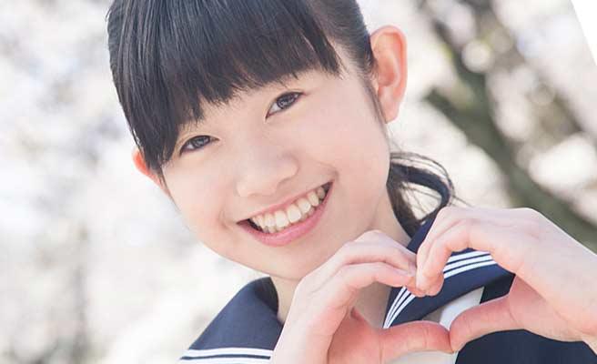 笑顔でハートマークを手で作る女子中学生
