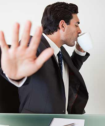 コーヒーを飲みながら片手で制止する男性