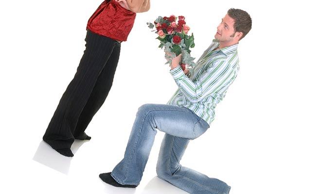 跪いて花束を女性に差し出す女性