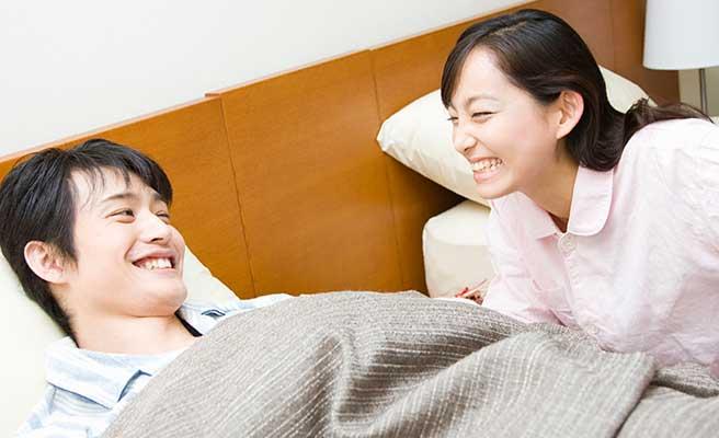 寝室で夫婦が和やかに会話している