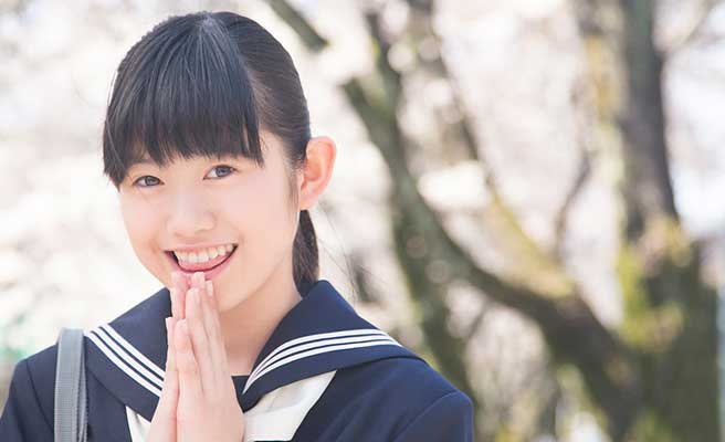 桜の木の下で手を合わせる女子中学生