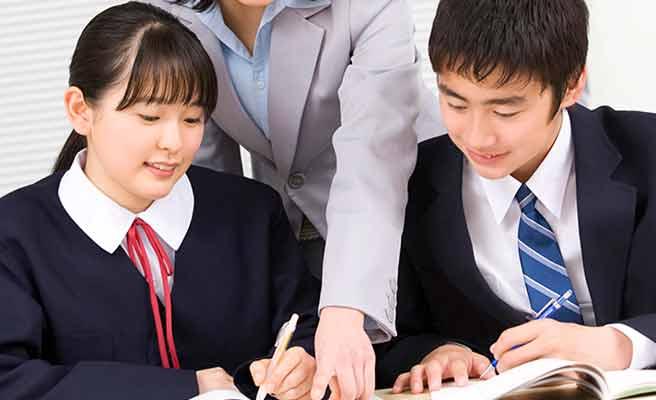 男女の中学生が隣同士で勉強している