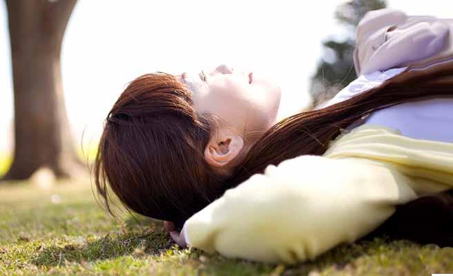 芝生の上に横になって空を見上げる女性