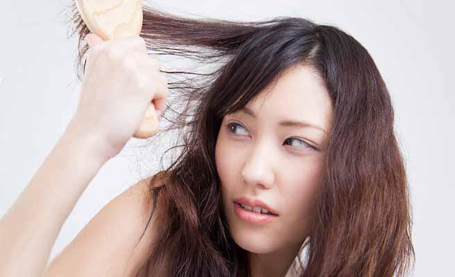 髪の毛を面倒くさそうにブラッシングする女性