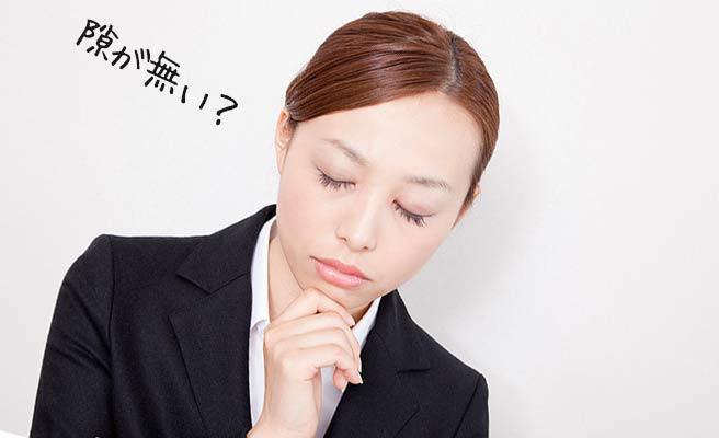 スーツ姿の女性が目を閉じて考える