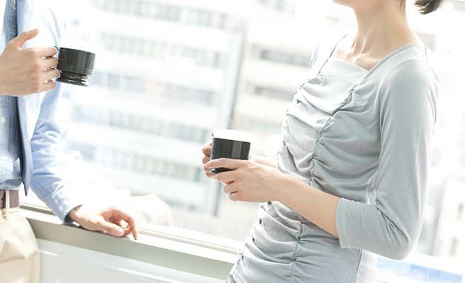 男性社員と向い合ってコーヒーを飲む女性
