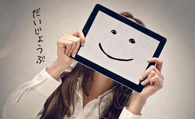 タブレットに映った笑顔を自分の顔の前に出す女性