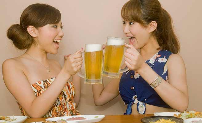 ビールジョッキで乾杯する女性二人